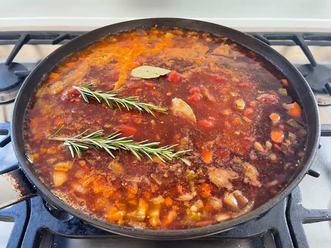 A frying pan with a dark liquid with diced sautéed vegetables, a tomato based sauce, bay leafs and sprigs of rosemary.
