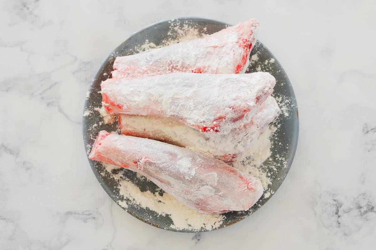Four raw lamb shanks covered in flour and seasoned with salt and pepper.