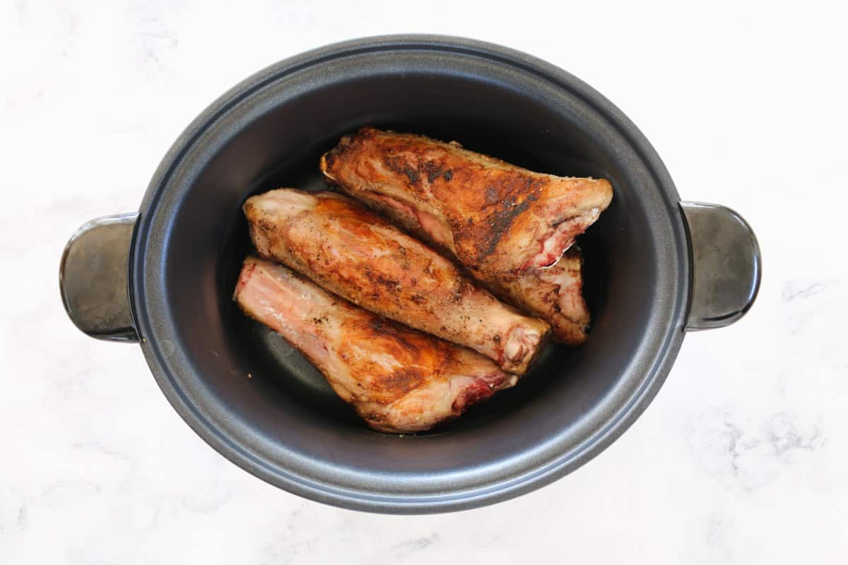 An oval slow cooker pot with seared lamb shanks inside.