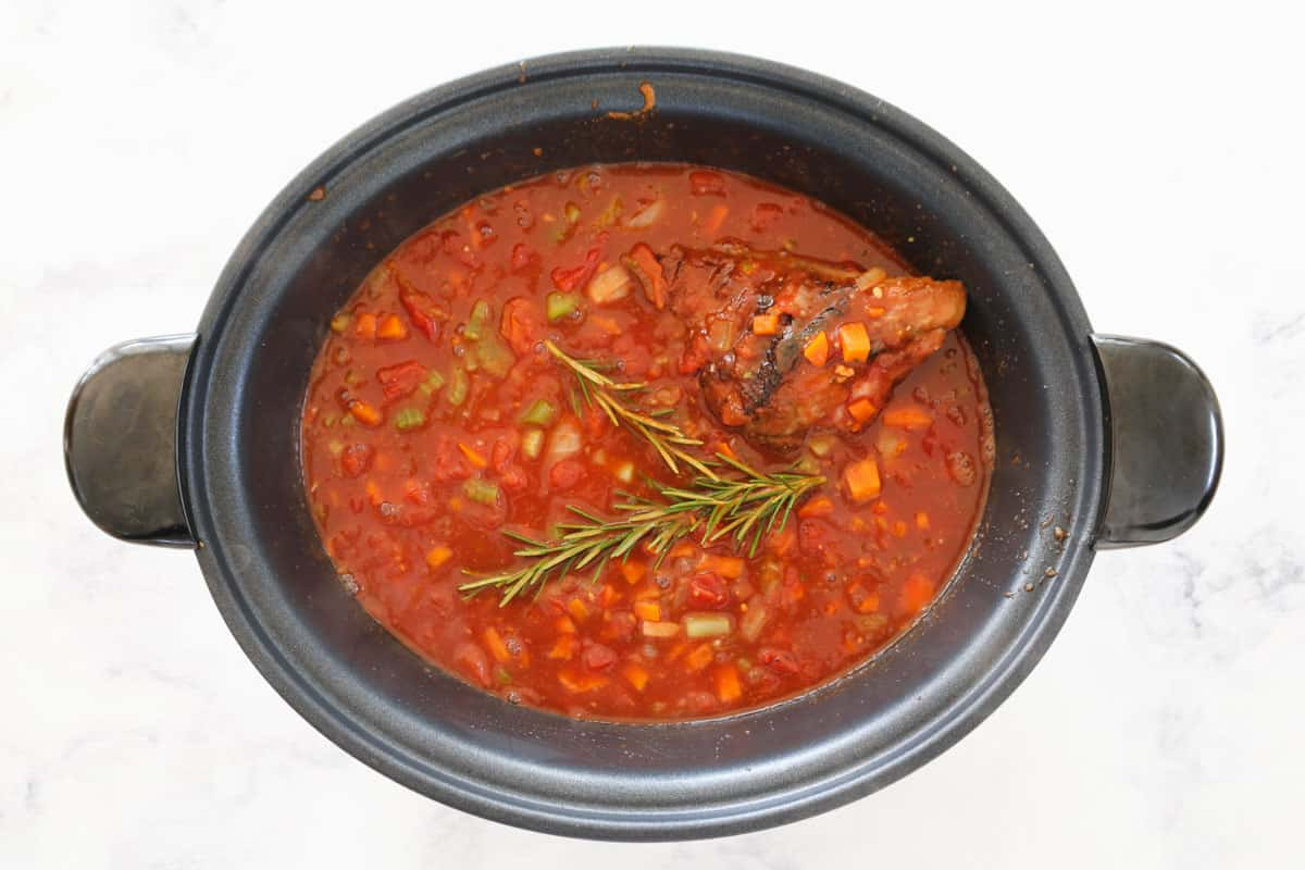 An oval slow cooker pot with a rich red casserole sauce, with a sprig of rosemary and a visible lamb shank.