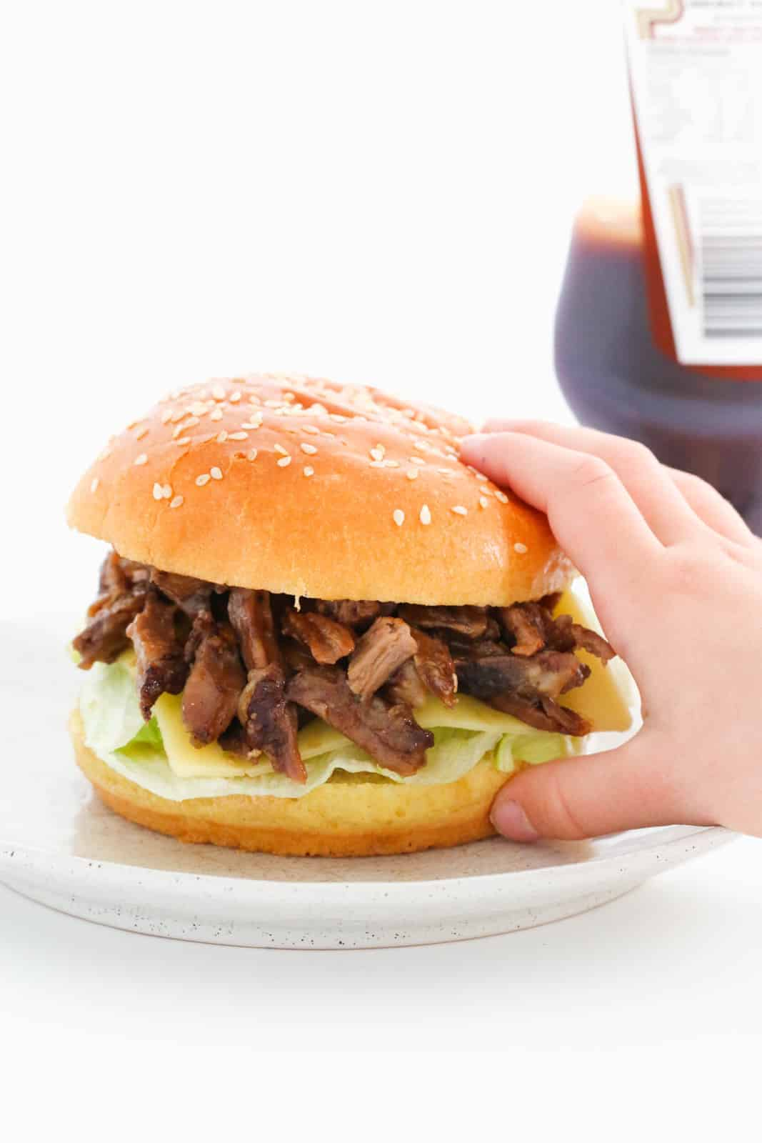 A hand picking up a burger filled with roast lamb, cheese and lettuce with BBQ sauce in the background.