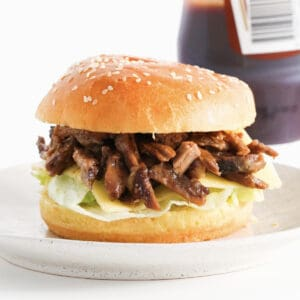 A pulled lamb burger with lettuce and cheese.