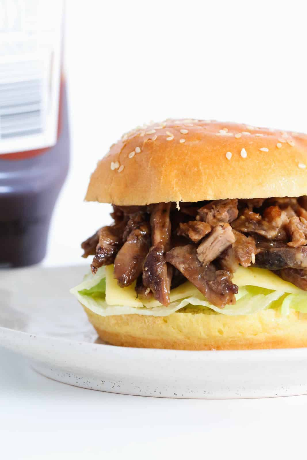 A burger filled with pieces of lamb, gravy, lettuce and cheese.