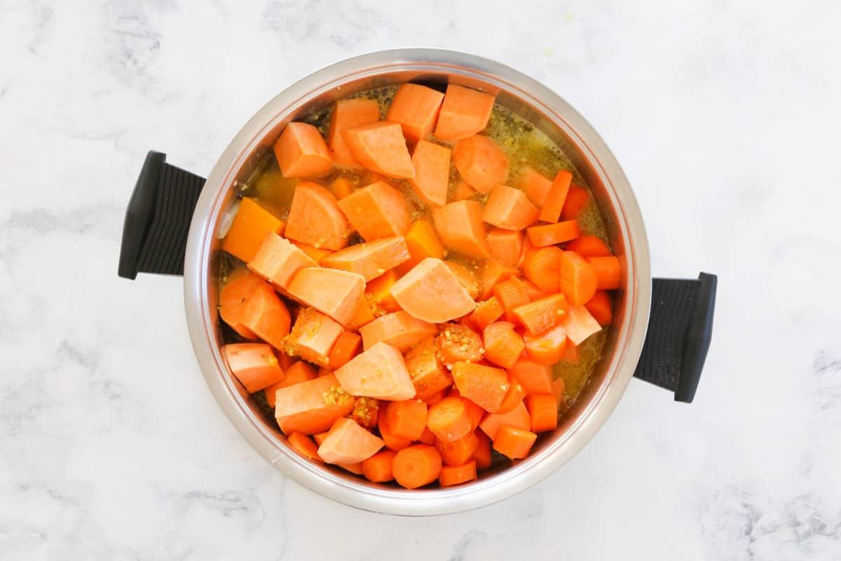 Chopped sweet potato, carrots and pumpkin in liquid stock in a black handled saucepan