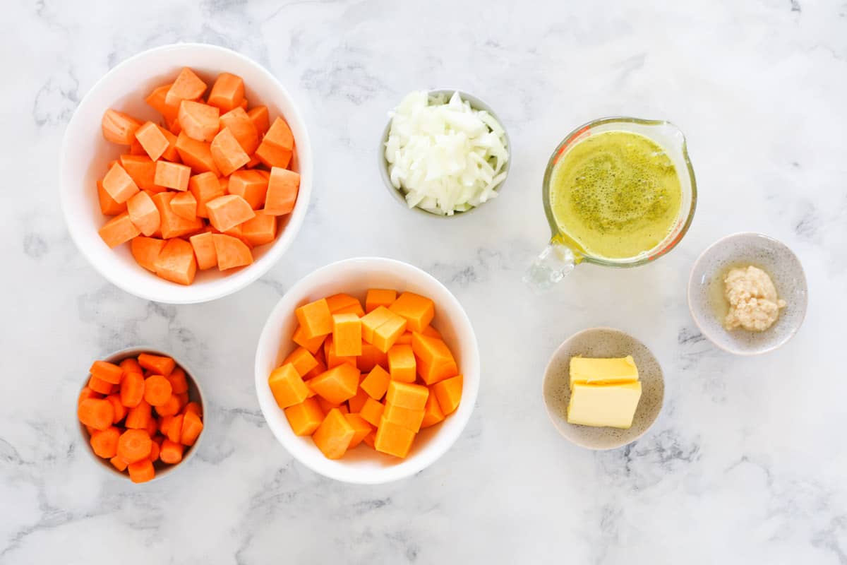 Individual bowls with sweet potato soup ingredients measured out on a marble bench top