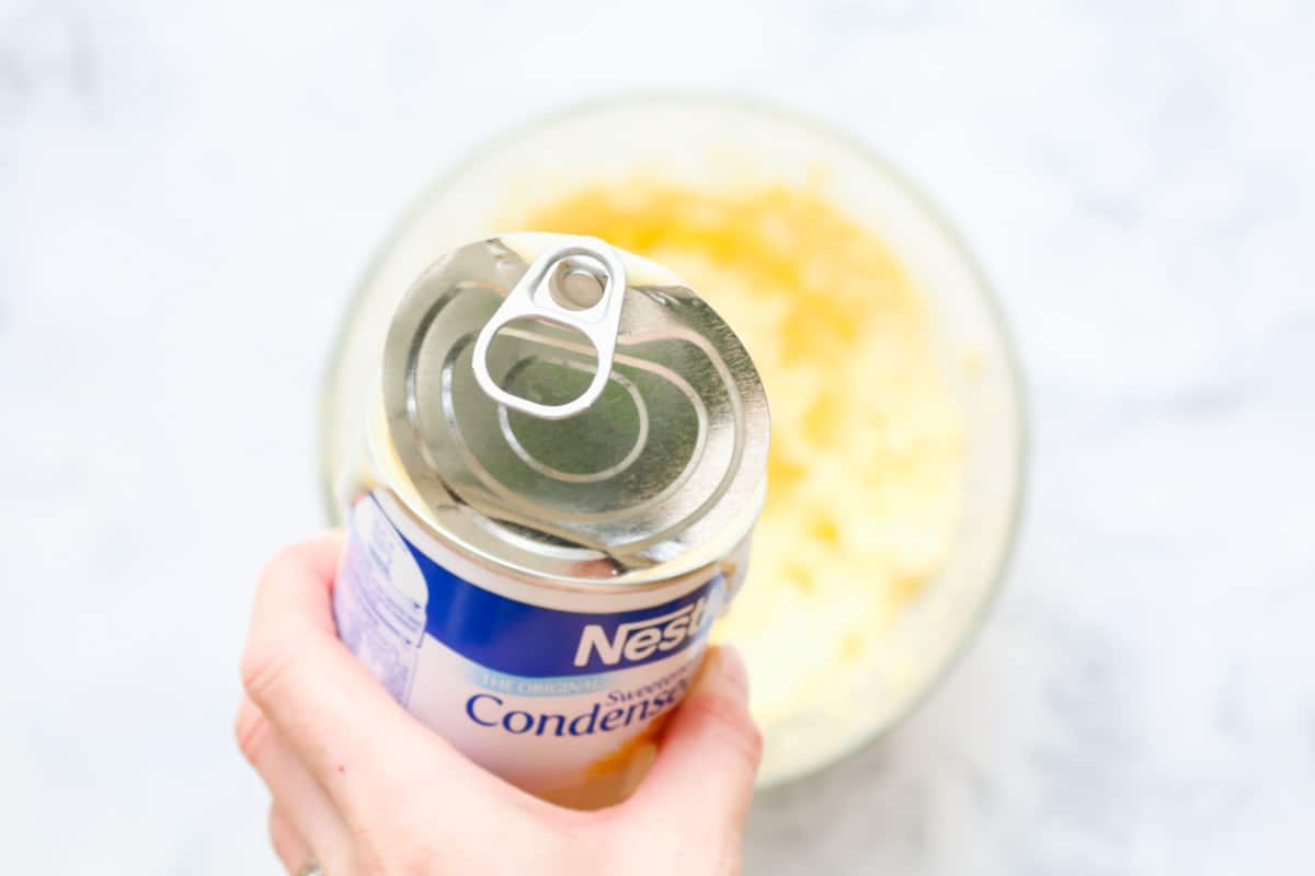 Condensed milk being added to mixture in a bowl.