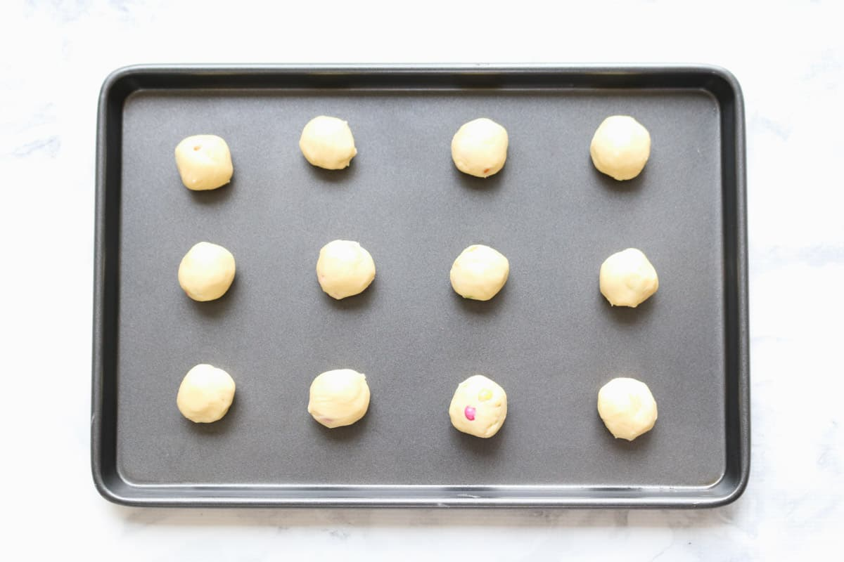 Rolled balls of cookie dough on a tray.