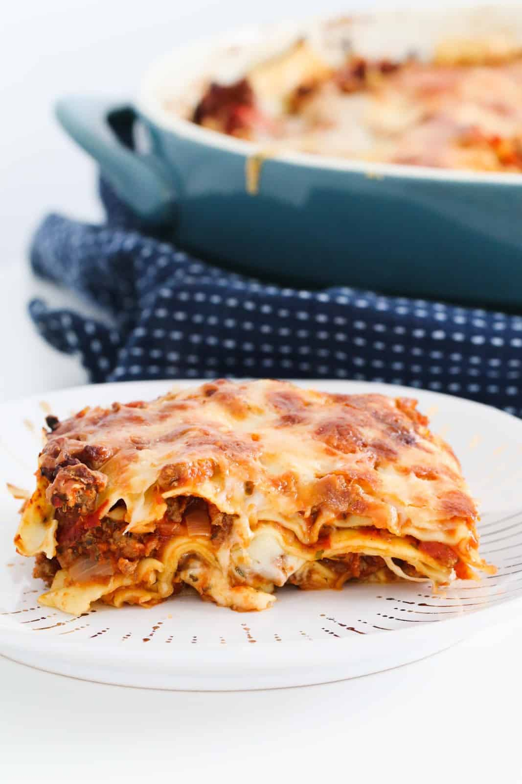Lasagne in a baking dish, resting on a tea towel with a serving of lasagne on a plate in the foreground.