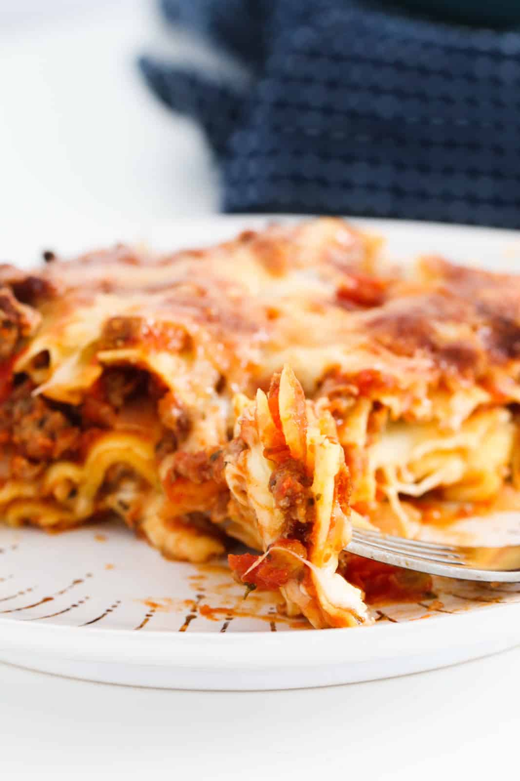 A closeup of a serving of lasagne with a piece on a fork in the foreground