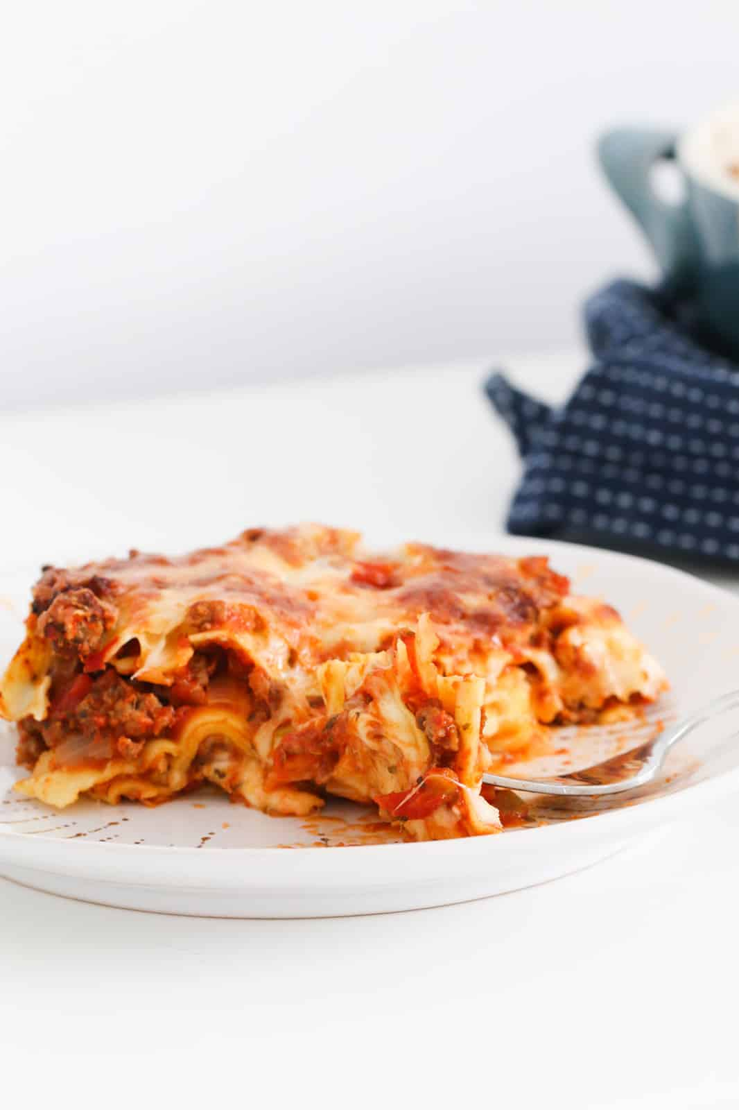 a serving of lasagne on a plate with a fork