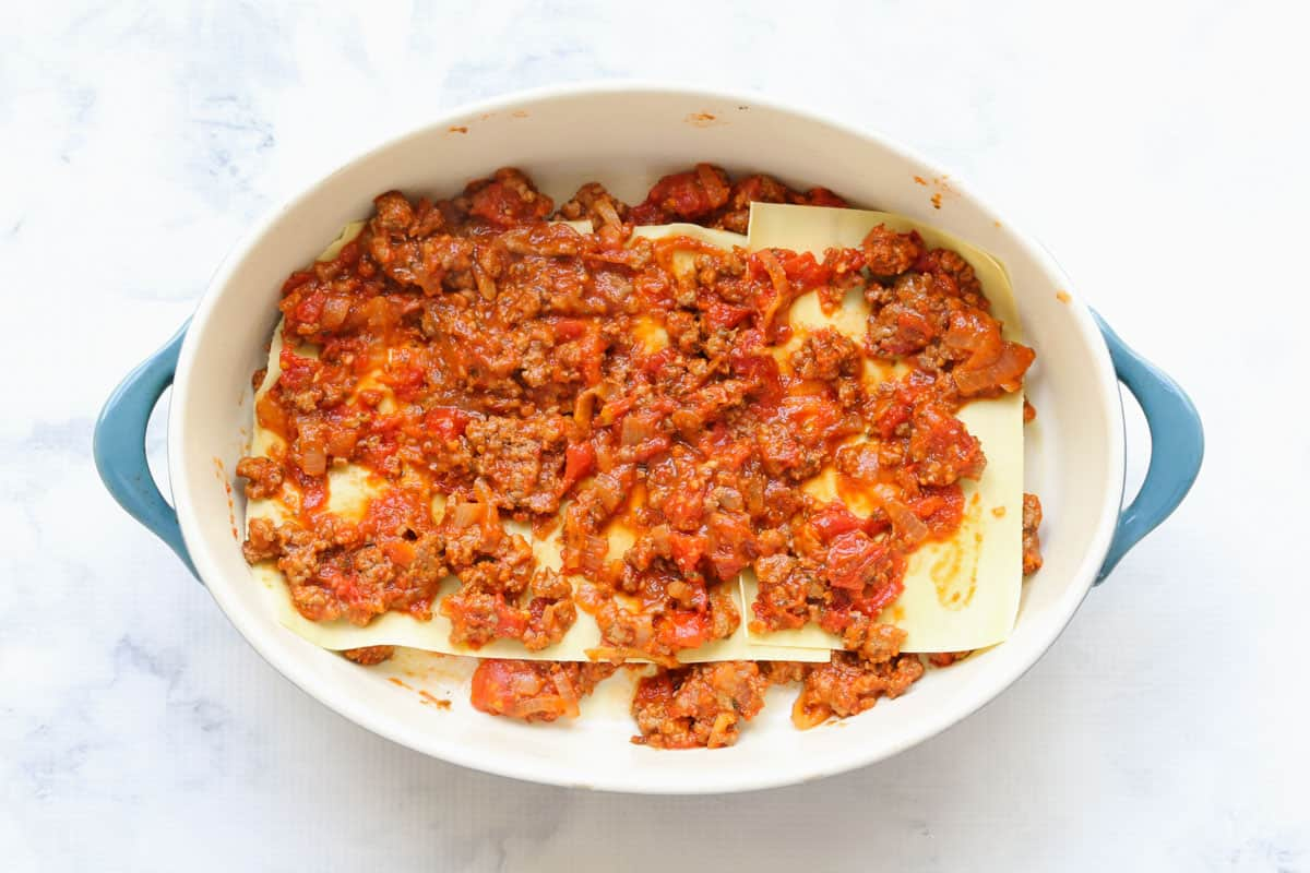 an oval baking dish with beef mince filling layered with lasagne sheets