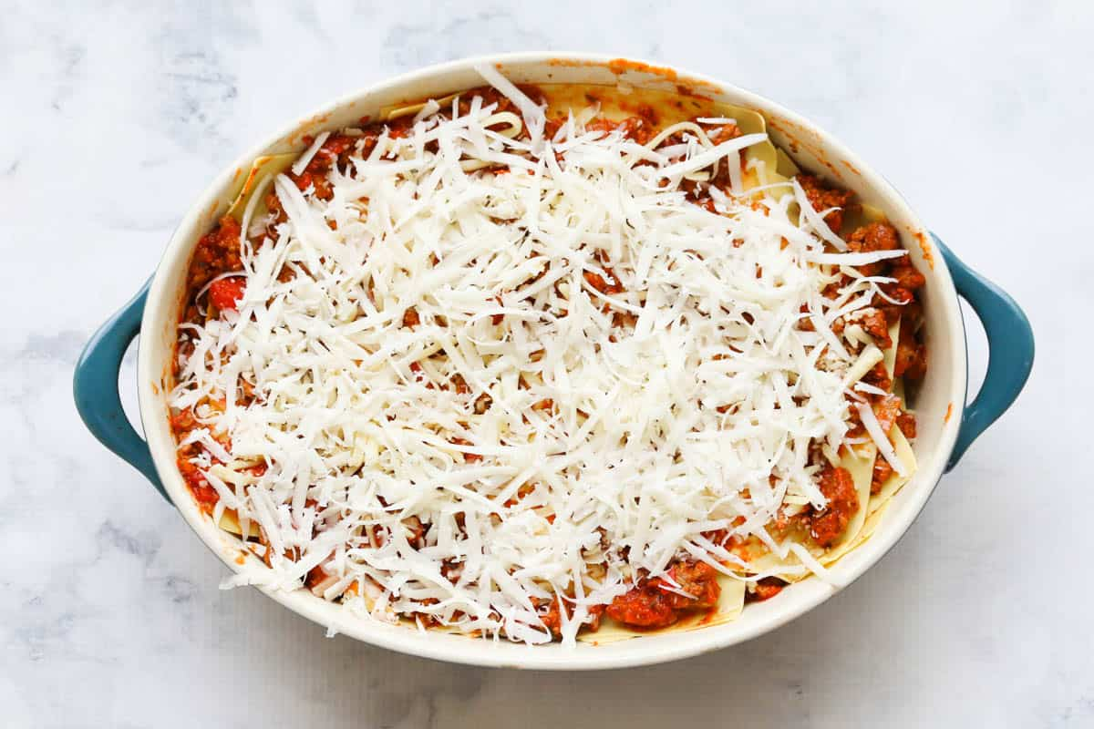 grated cheese layered on top of a beef lasagne