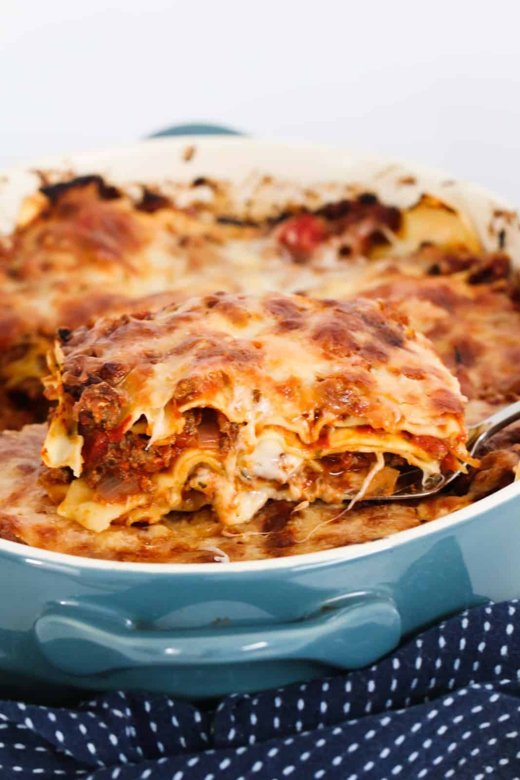 A baking dish of lasagne, with a tea towel wrapped around it, and a large spoon lifting some out of the dish
