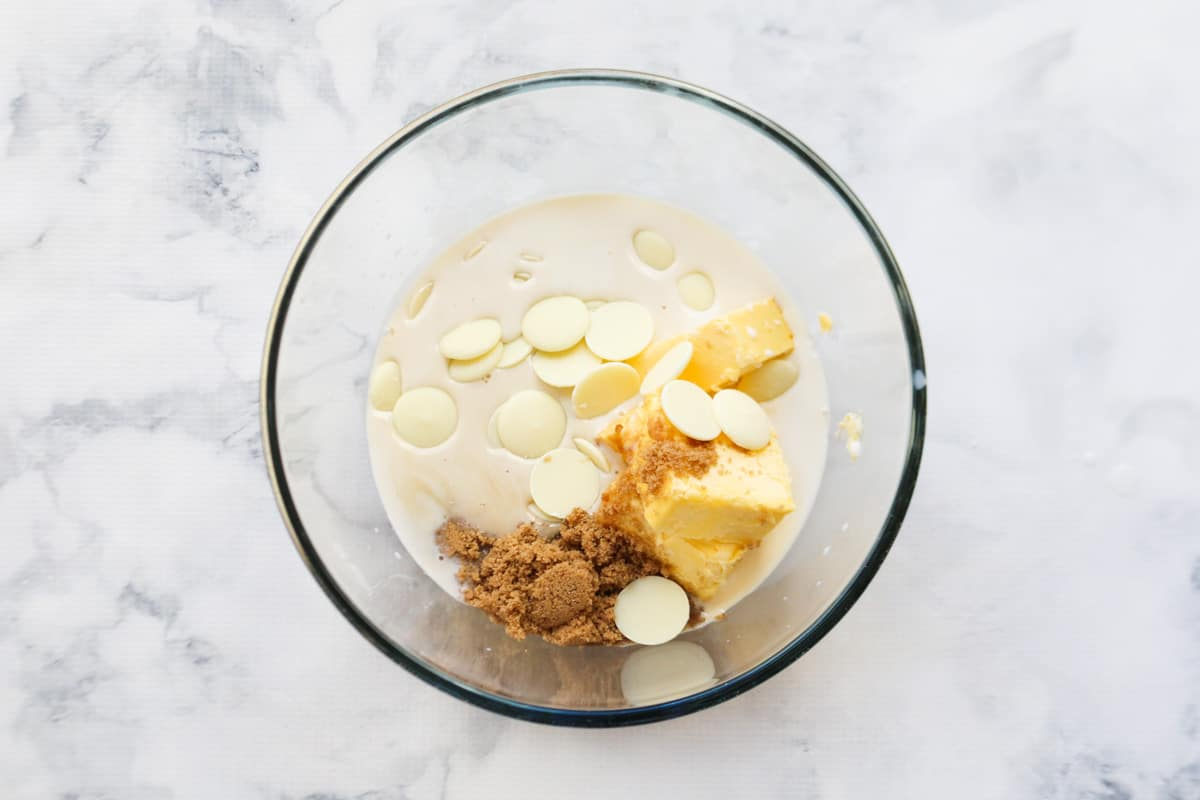Butter, brown sugar, white chocolate melts and milk placed in a glass bowl