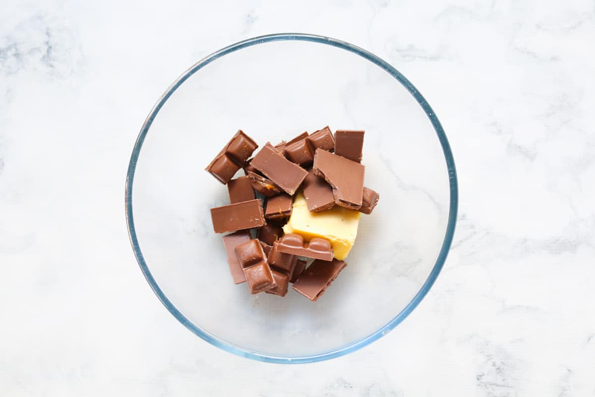 A bowl with broken up pieces of Caramello chocolate and butter