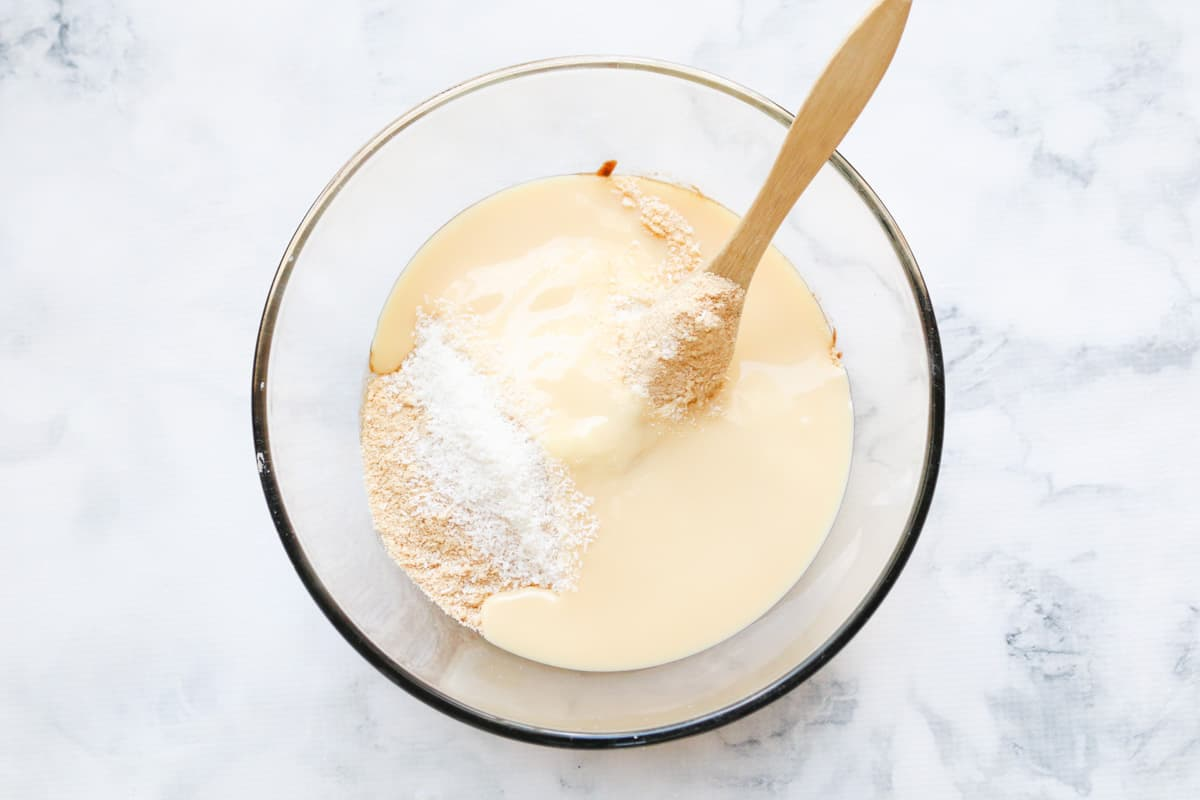 A glass bowl with crushed biscuits, desiccated coconut and condensed milk in it.