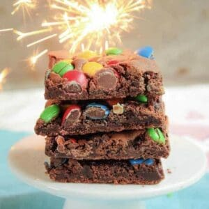 Front view of a stack of brownies with M&Ms and sparkler in background