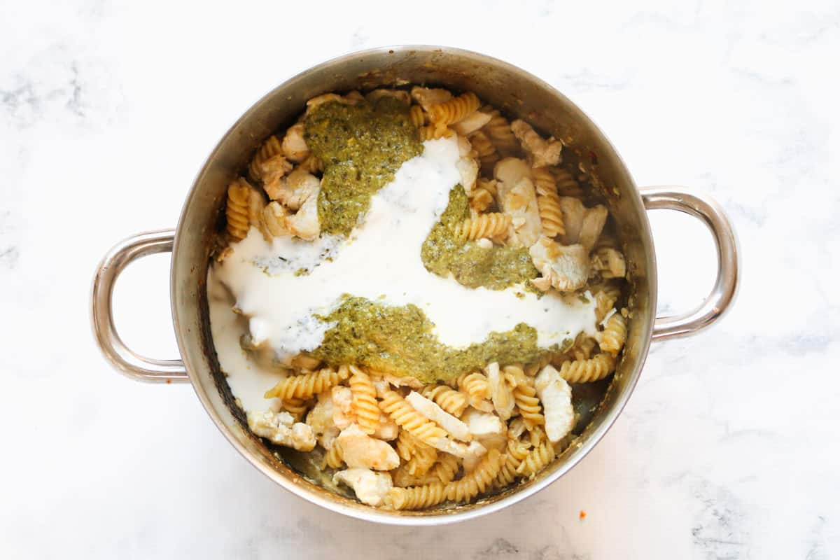 Cream and pesto poured over chicken and pasta in a saucepan.