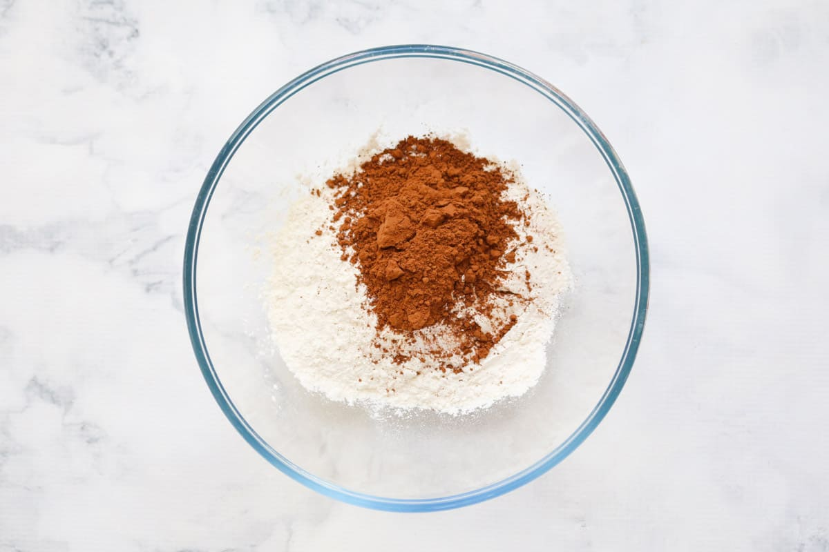 Self raising flour and cocoa powder in a glass bowl