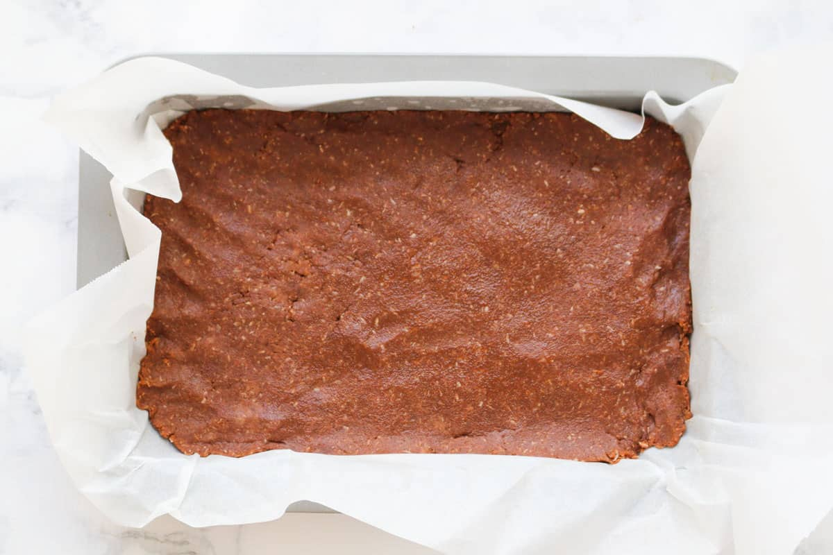 A chocolate base mixture pressed into a lined slice baking tin.