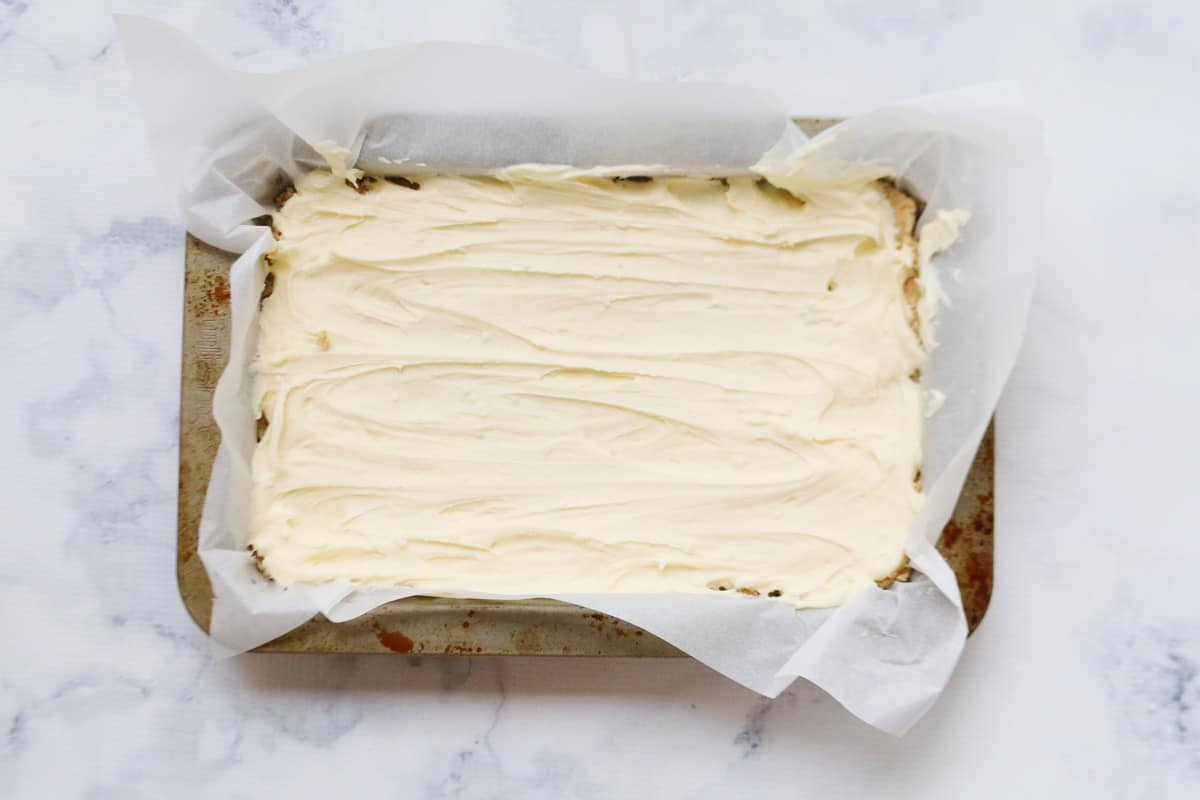 An iced slice in a baking tin lined with baking paper