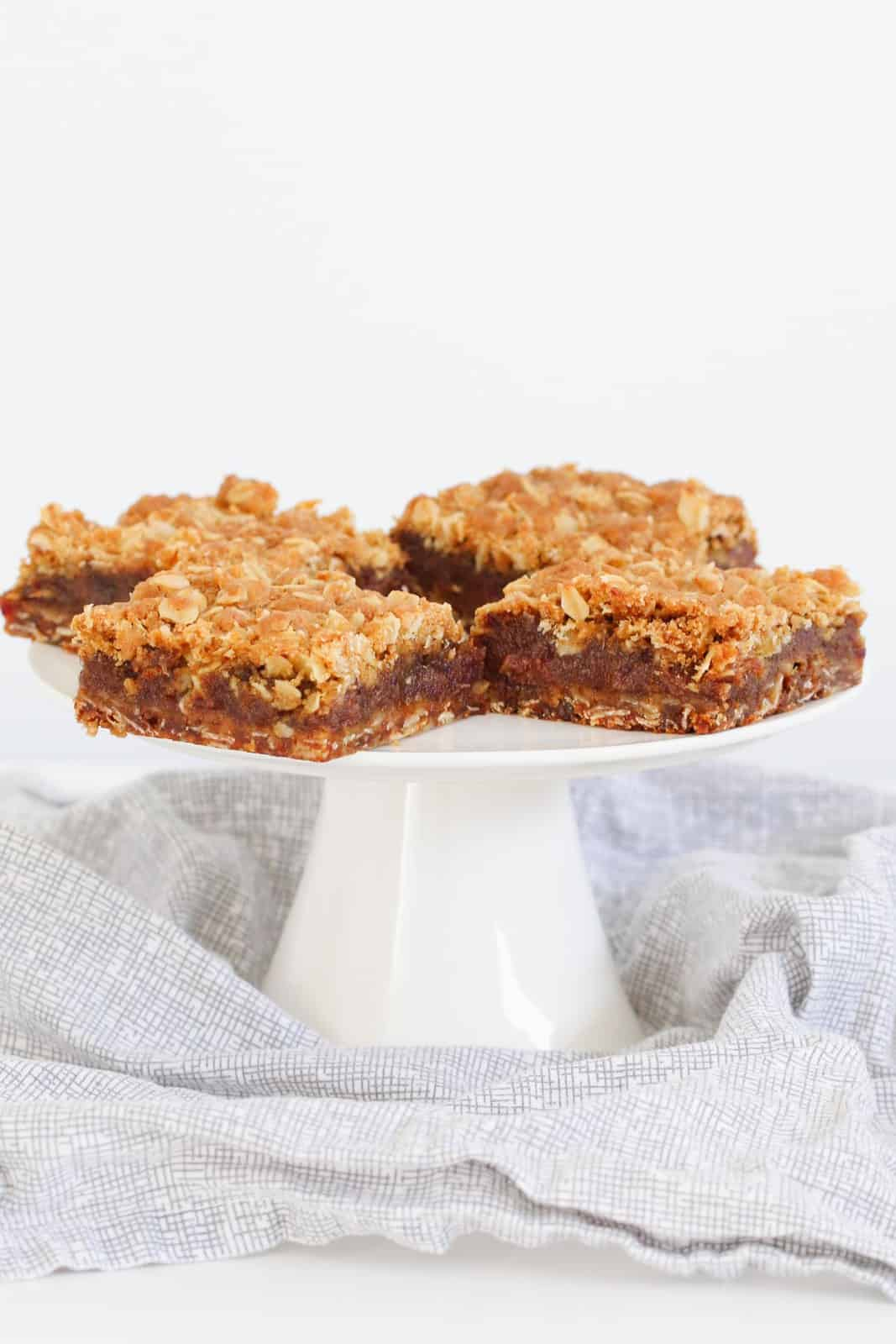Four squares of a crumble and date slice, served on a white cake stand
