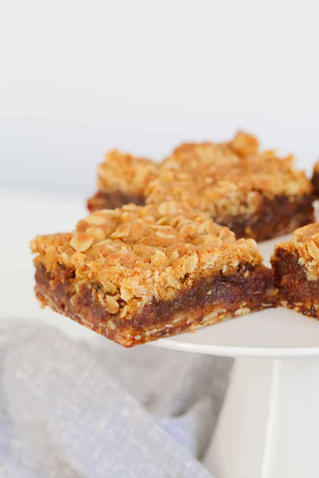 A layered slice filled with dates and a rolled oats crumble topping