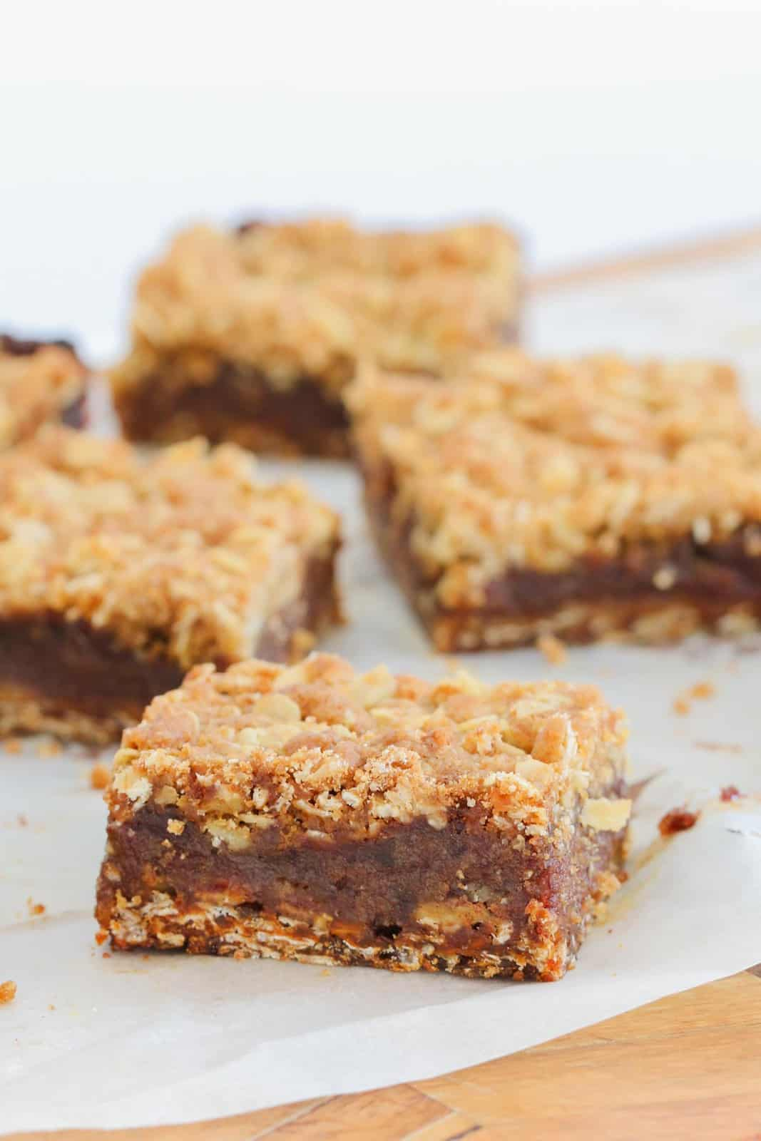 Squares of a oat & date slice on a white dish, with a golden crumble topping