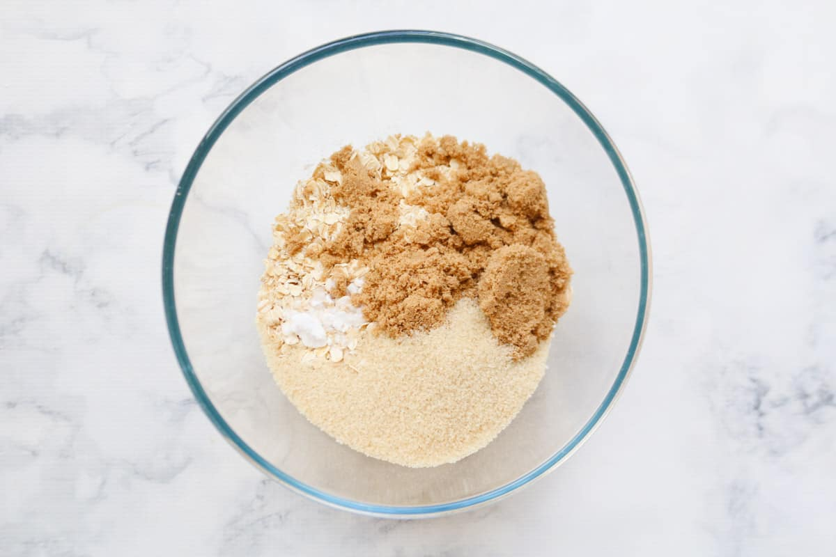 Brown and raw sugar added to oats and flour in a glass bowl