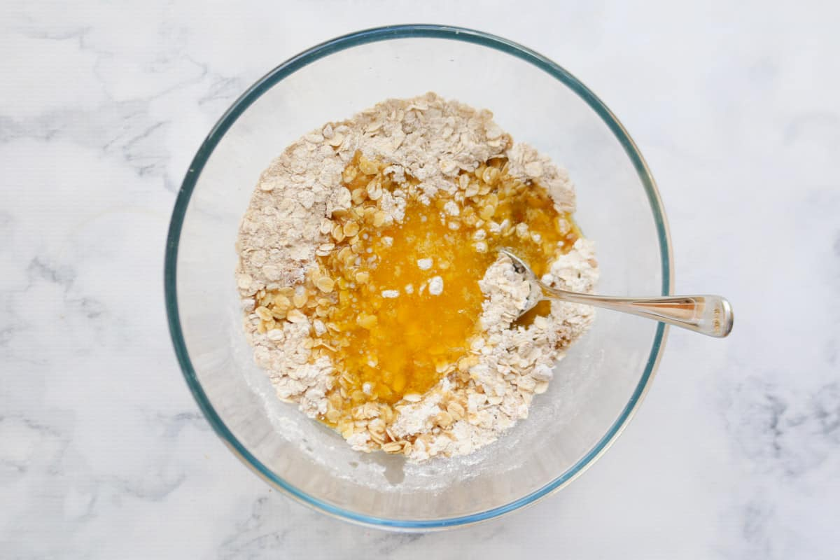 Melted butter added to dry ingredients in a glass bowl