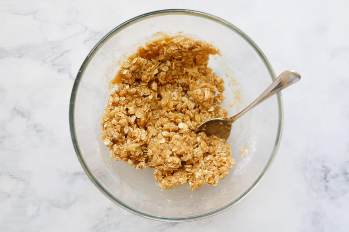 The rolled oats mixture in a glass bowl with a spoon
