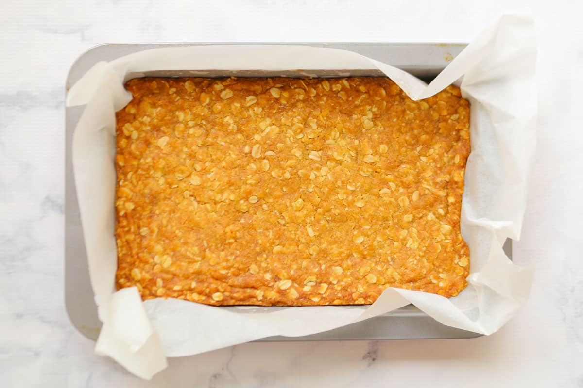 The base layer of date squares baked golden in a slice tin.