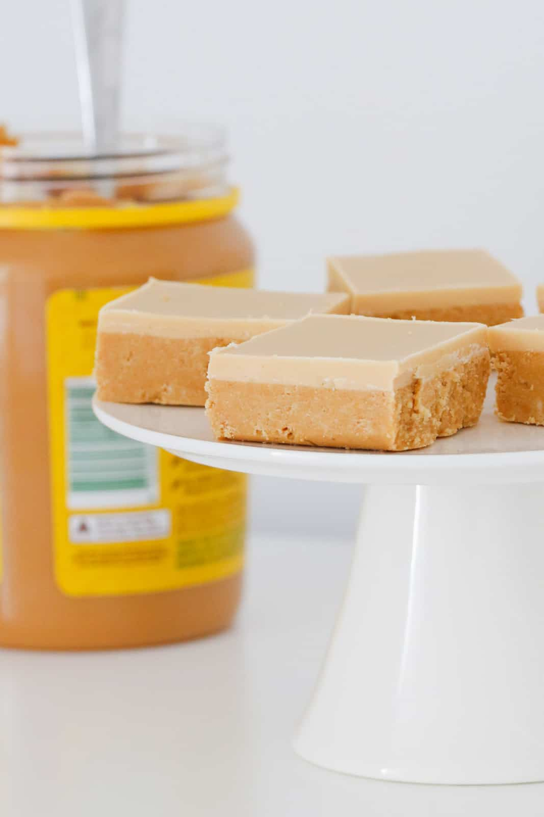 A jar of peanut butter behind a cake stand topped with squares of slice topped with a white chocolate and peanut butter icing.