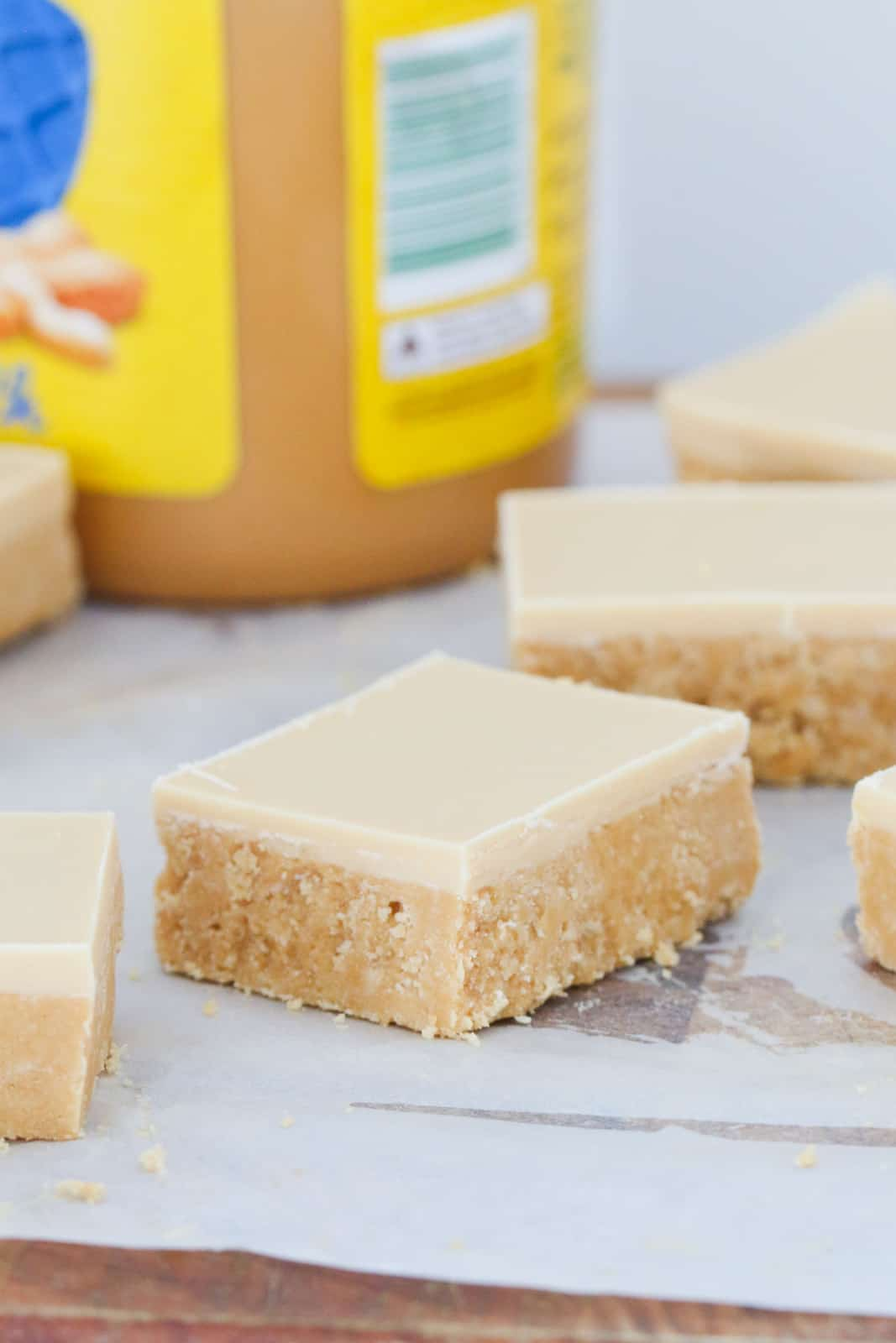 Squares of peanut butter slice topped with white chocolate and peanut butter topping.