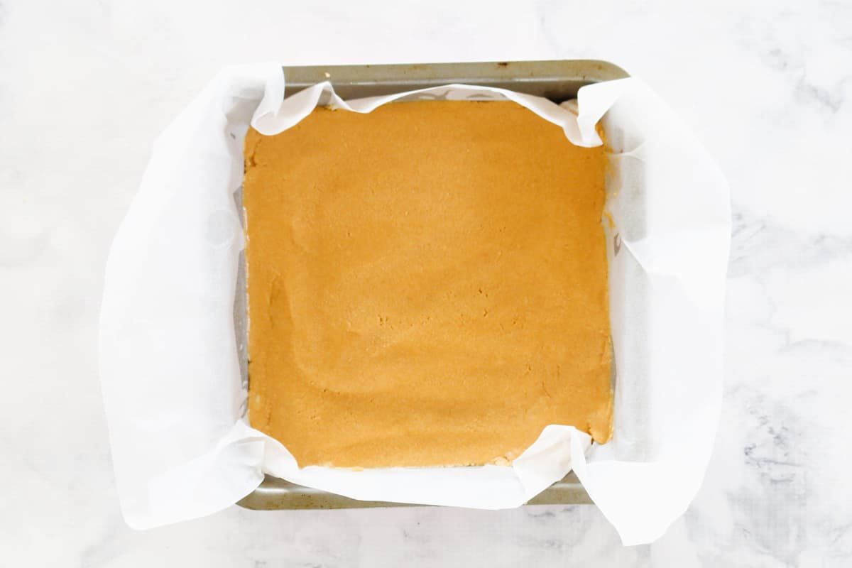 A slice mixture pressed into a baking paper lined tin.