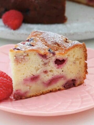 Front view of slice of cake on pink plate with two raspberries