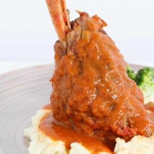 A close up image of a slow cooker lamb shank on mashed potato