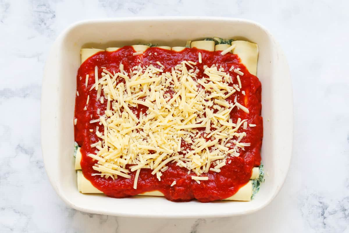 Grated cheese sprinkled over the top of tomato passata and filled pasta tubes