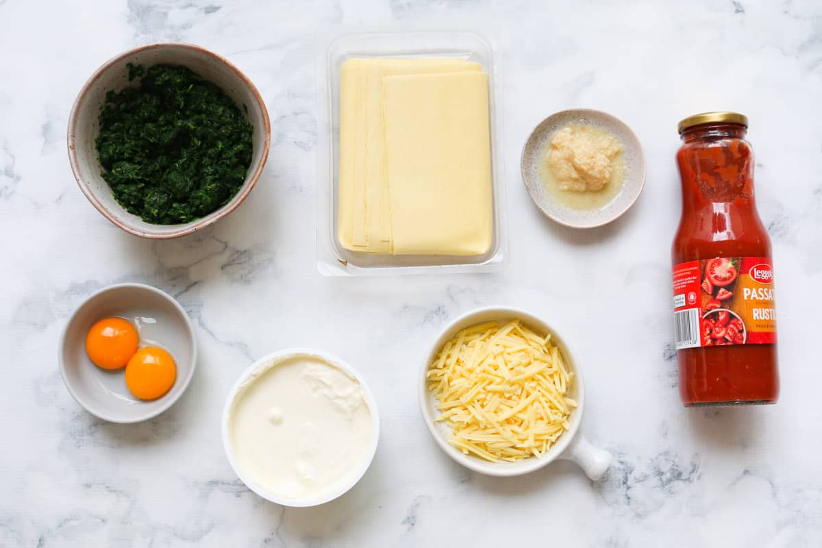 Ingredients for spinach and ricotta cannelloni laid out on a marble counter