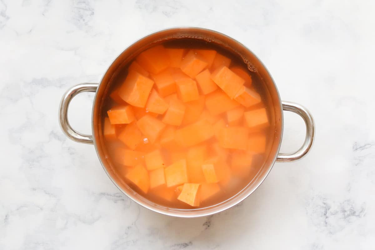 A pot with chopped sweet potato in water