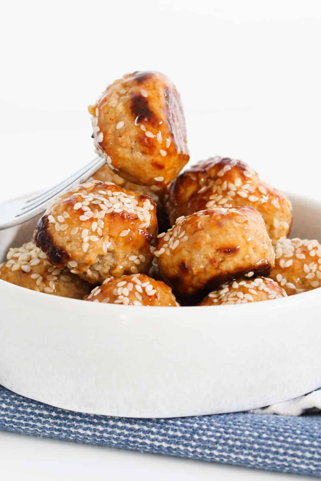 A fork picking up a chicken meatball coated in sweet chilli sauce and sesame seeds.