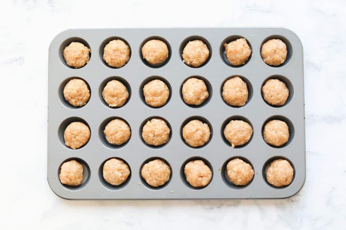 Chicken meatballs in a mini muffin tray.