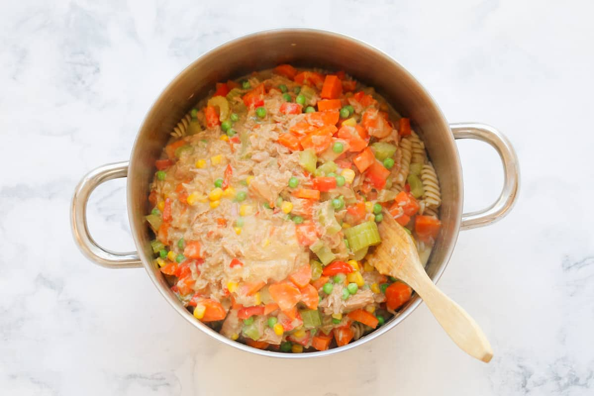 A cooking pot with a wooden spatula stirring pasta, vegetables, tuna and a creamy soup together