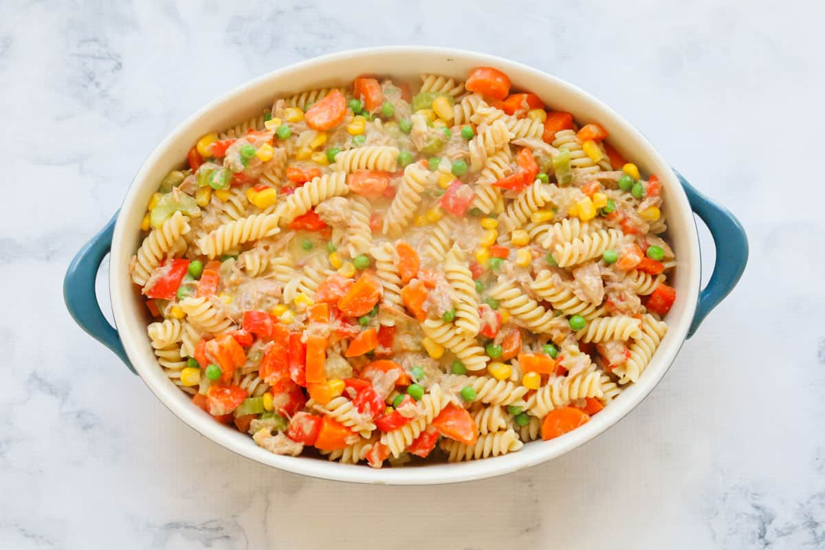 An oval baking dish with a pasta, tuna and vegetable filling