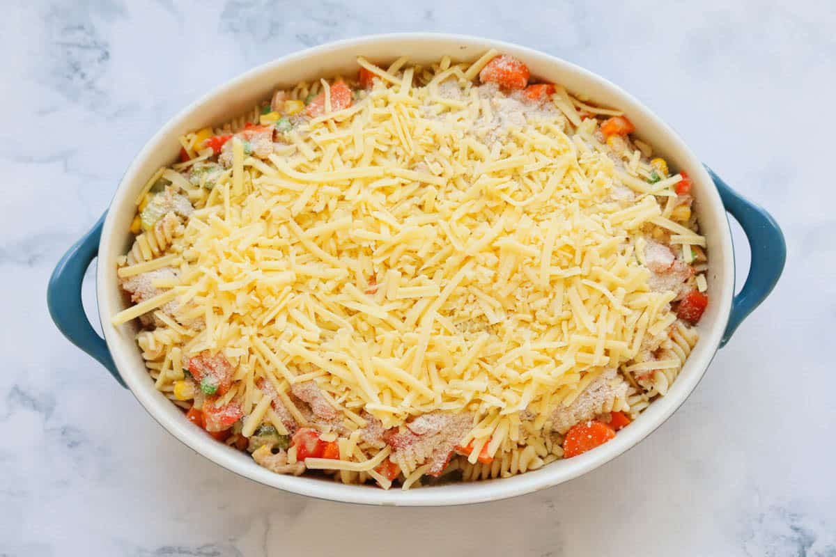 A blue oval baking dish filled with a cheese topped casserole ready to bake