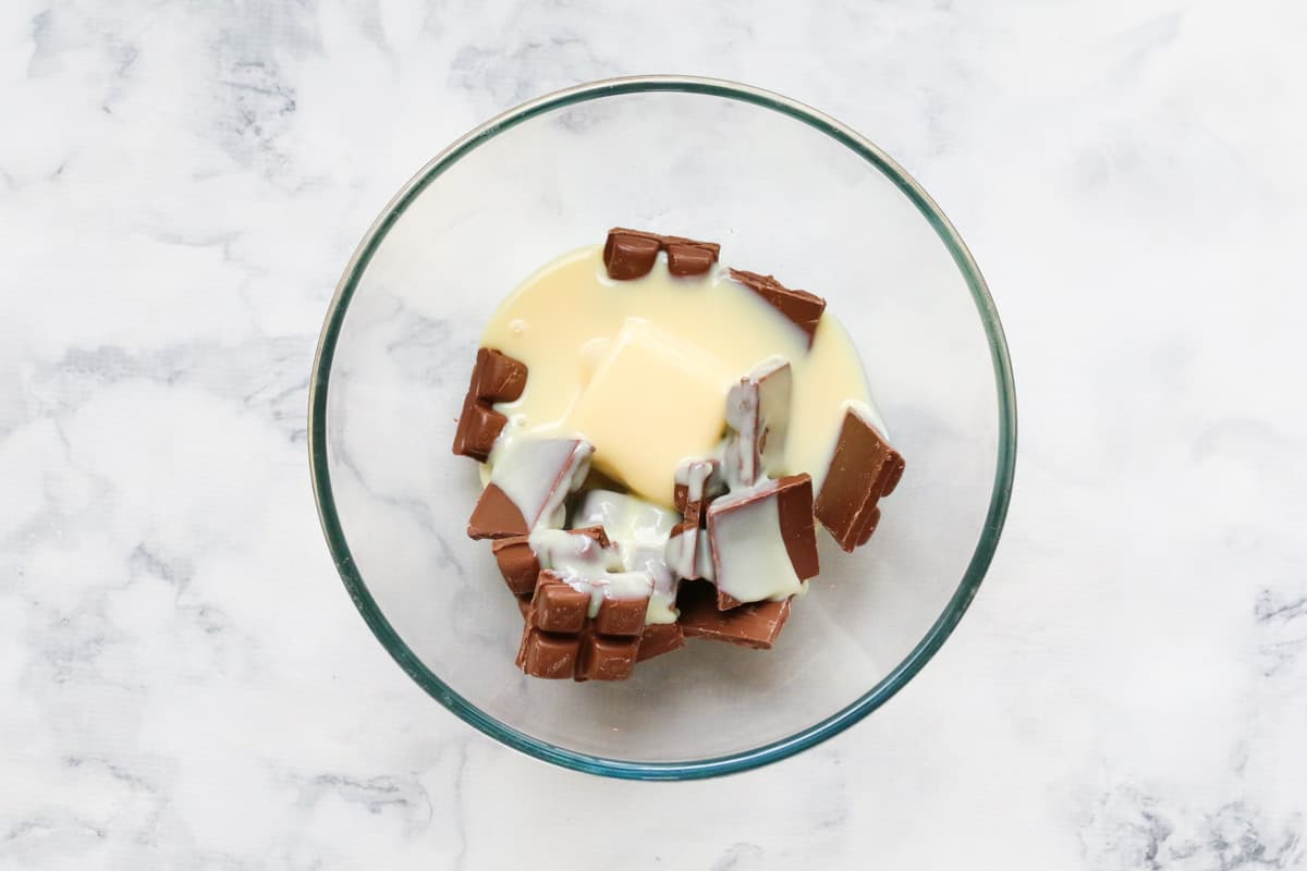 A glass bowl with chocolate, butter and condensed milk in it.