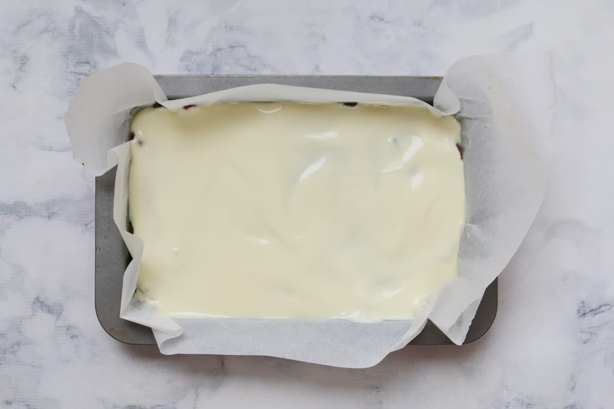 Turkish Delight slice in a tin with baking paper covered in white chocolate