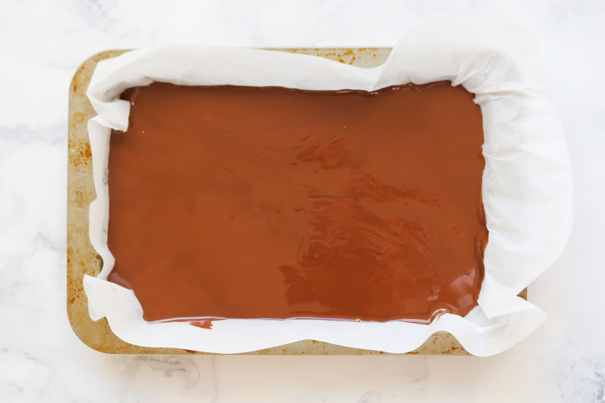 Melted chocolate covering slice in a rectangular slice tin.