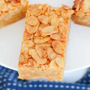 A close up view of a piece of honey almond slice on a white plate