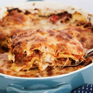 a baking dish of lasagne, with a tea towel wrapped around it, with a serving being lifted out